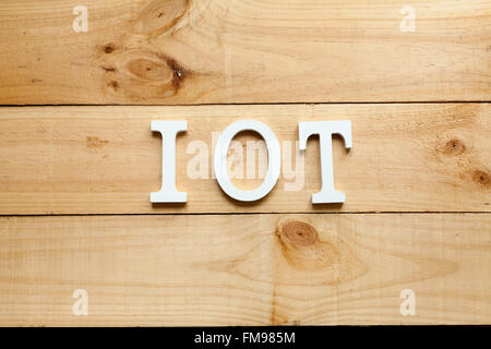 The acronym IOT Internet of things on wooden background - Stock Photo