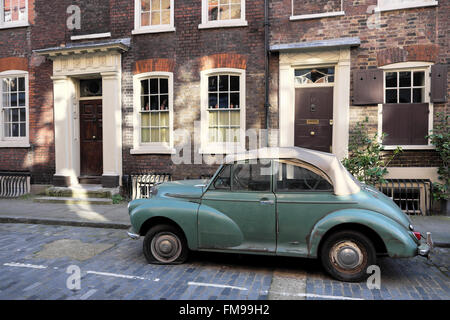 Morris Minor car with a flat tire parked on Elder Street in Spitalfields, London E1  KATHY DEWITT - Stock Photo