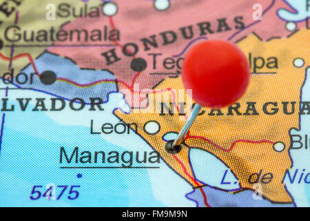 Close-up of a red pushpin in a map of Managua, Nicaragua. - Stock Photo