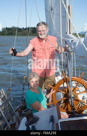 Portrait of a happy retired couple on their classic ketch on a lake under sunny skies. - Stock Photo