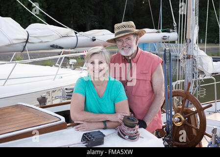 Portrait of a happy retired couple on their classic ketch moored at their slip. - Stock Photo