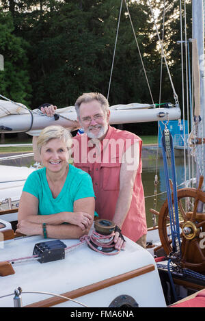 Portrait of a happy retired couple on their classic ketch as the late summer sun sets behind a grove of trees. - Stock Photo