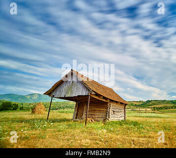 Time Lapse countryside landscape with old small barn, yellow field and varied nature. - Stock Photo