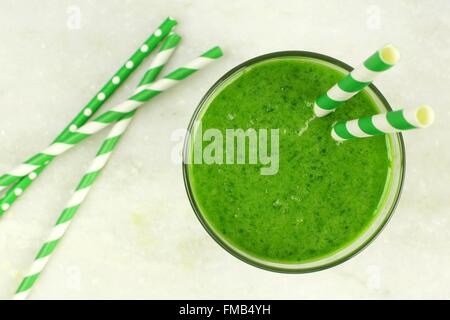 Green smoothie downward view in glass with straws on white marble background - Stock Photo