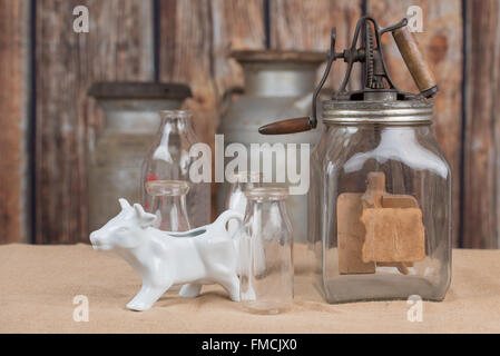 Old dairy products arranged in a rustic scene - Stock Photo