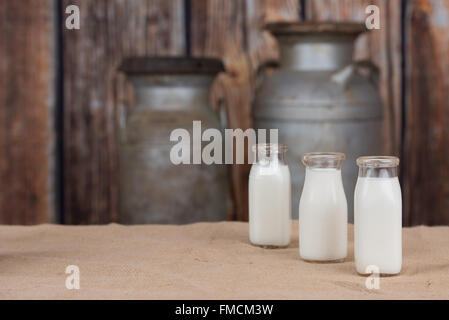 Three old bottles of milk lined up on right side. Empty space on left - Stock Photo