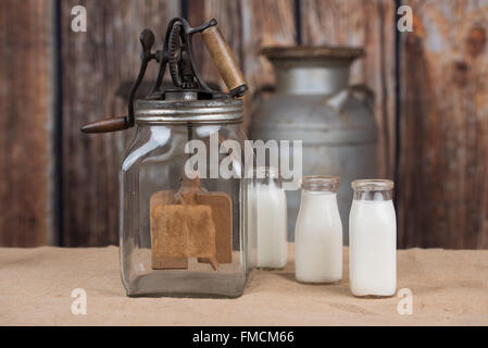 Butter churn with bottles of milk - Stock Photo
