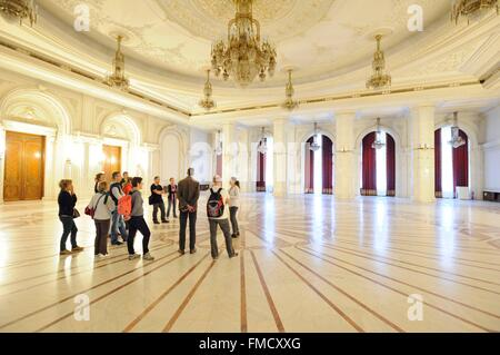 Romania, Muntenia, Bucharest, the Parliament Palace which is the former palace of Ceausescu, tourists in a room - Stock Photo