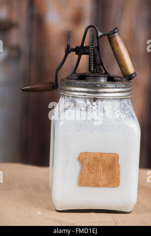 Old butter churn filled with cream - Stock Photo