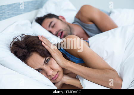 Woman blocking ears with hands while man snoring on bed - Stock Photo