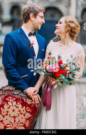 Happy groom and bride lovingly look at each other and smile - Stock Photo
