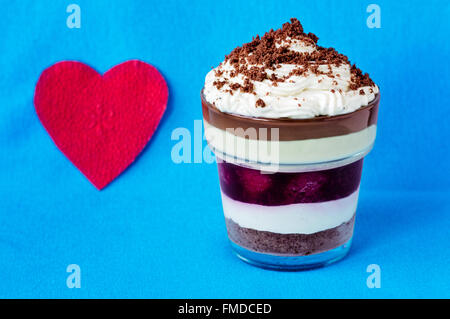 Romantic layered dessert with crumbled cookies on top near a heart shaped red napkin on a light blue background. - Stock Photo