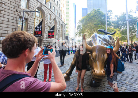 NEW YORK CITY - SEP 16: Charging Bull sculpture and tourists on SEP 16, 2014 in New York City. The sculpture is - Stock Photo