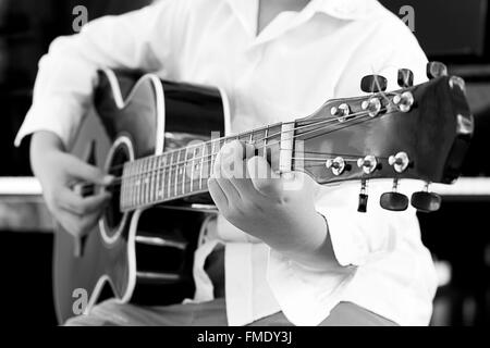 asian young boy learning to  play a Guitar - Stock Photo