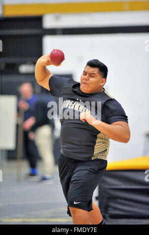 A high school athlete straining in throwing the shot put during an indoor track meet. USA. - Stock Photo