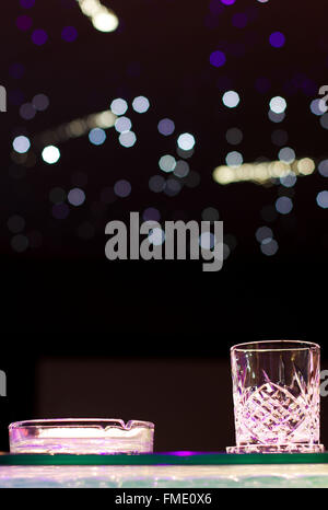Glass of whiskey and ashtray on top of the bar - Stock Photo