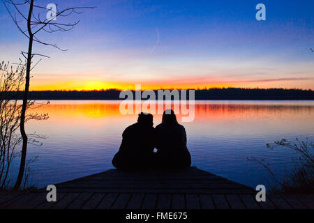 lovers sitting in front of a lake, watching the beautiful sunset - Stock Photo