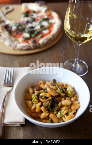 A bowl of white bean, romanesco and mussels soup with white wine and a pizza on the table behind it.