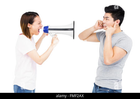 Angry woman shouting at young man on horn loudspeaker - Stock Photo