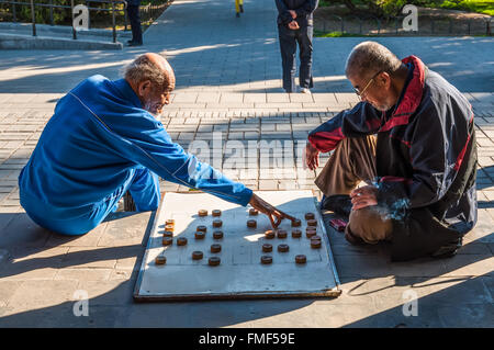 Elderly Chinese men playing Chinese chess called Xiangqi in a park outside the Temple of Heaven, Beijing, China - Stock Photo