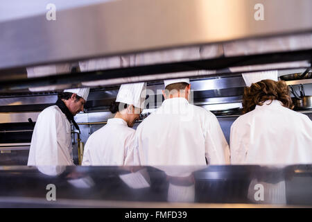 Group of chefs in white uniform busy to preparing food - Stock Photo