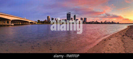 pink hour of sunrise over Perth city CBD. View across swan river from sandy beach towards downtown with the bridge. - Stock Photo