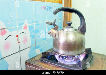 steel Kettle old boils  on a gas stove - Stock Photo
