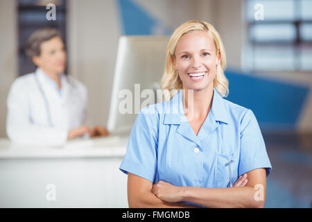 Portrait of pretty female doctor with arms crossed - Stock Photo