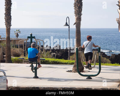 Outdoors exercise apparatus in use on the coastal promenade in Playa San Juan, Tenerife, Canary Islands Spain, active - Stock Photo