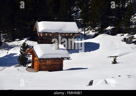 Two Traditional Alpine Hut in Snow Filled Meadow in Corvara Italian Dolomites - Stock Photo