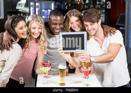 Happy friends taking selfie with tablet - Stock Photo