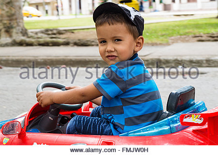 Boy child riding a toy go kart rental in city's main plaza - Stock Photo