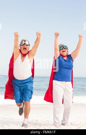 Senior couple wearing superman costume - Stock Photo