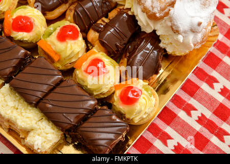 Eclair and a lot of cakes on a table - Stock Photo
