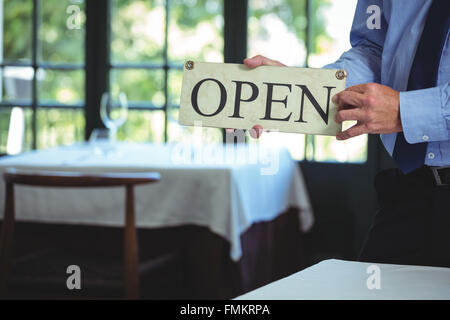 Businessman holding open sign - Stock Photo