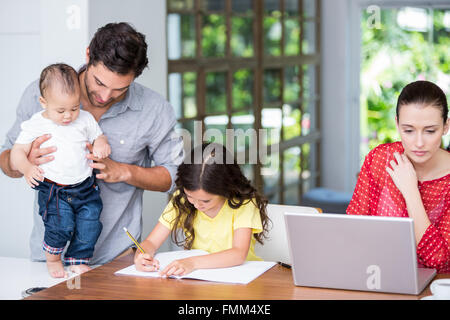 Mother using laptop daughter doing homework with father - Stock Photo