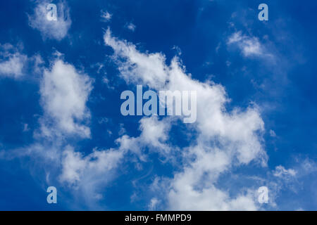 White fluffy and wispy clouds in blue sky - Stock Photo