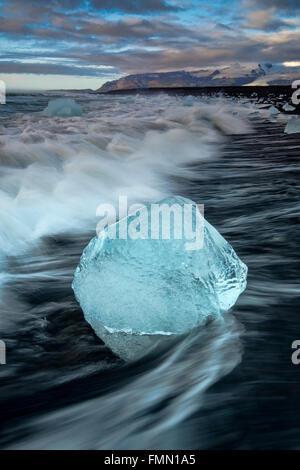 Heavy Seas wash Icebergs up on Jokulsa Volcanic Beach at Dawn, Jokulsarlon, Near Hofn, Southern Iceland - Stock Photo