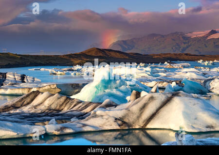 Rainbow over Icebergs in Jokulsarlon Glacial Lagoon, Jokulsarlon, Near Hofn, Southern Iceland - Stock Photo