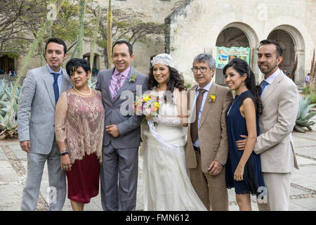 Mexican wedding party pose for portrait on Santo Domingo church plaza with smiling bride holding small bouquet spring - Stock Photo