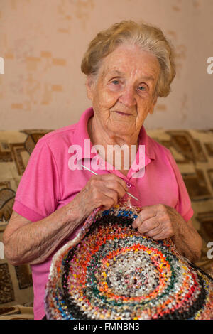 An old woman sits knitting a rug. - Stock Photo