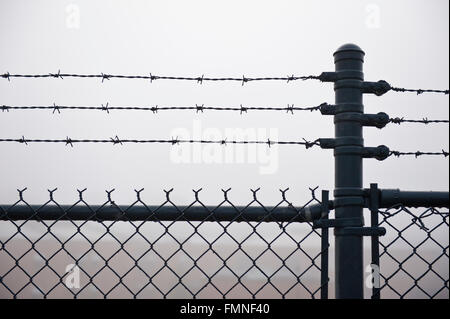 Wet Barbed Wire Fence In Dense Fog - Stock Photo