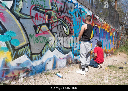 Graffiti artists spray paining on a wall at the Austin Graffiti Park ...