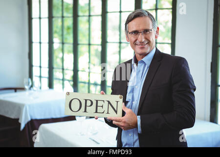 Smiling businessman holding open sign - Stock Photo