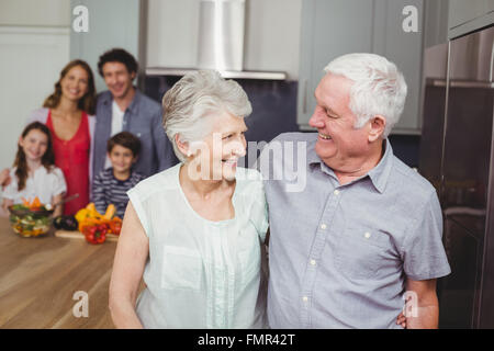 Happy grandparents with family in kitchen - Stock Photo