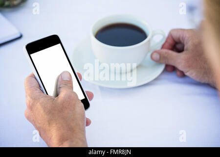 Close up of masculine hands using smartphone and having coffee - Stock Photo