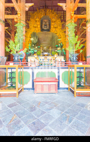 Front of the centered largest bronze Daibutsu statue and altar inside Great Buddha Hall, Daibutsuden, at Todai-ji - Stock Photo
