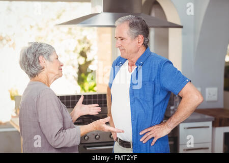 Side view of senior couple arguing in kitchen - Stock Photo