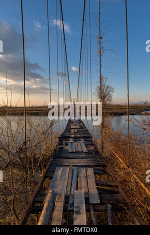 Old suspension bridge with broked wooden planks during sunset.