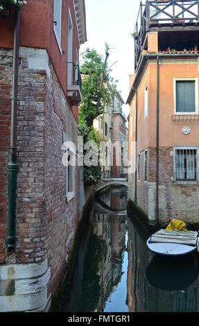 A small canal running between two old buildings in Venice. A boat is moored to one side; a bridge arches over the - Stock Photo